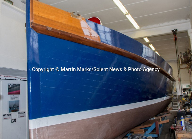 Pictured:  Stages of repainting the hull.<br /> <br /> An historic 100 year old Royal Navy steam ship has finally been returned to its former glory after a painstaking restoration process.<br /> <br /> The 50ft-long Steam Pinnace 199 is believed to be the last remaining boat of its type in operational service.<br /> <br /> For years, the significance of the boat, which was built in 1911, was lost on various owners and it languished at the side of the Thames for more than 20 years as a static houseboat.<br /> <br /> Her steam engine was even replaced by a petrol engine.<br /> <br /> However, before the vessel disappeared forever beneath a Thames mud bank, she was recognised for the proud little ship she once was and rescued by a group of volunteers, who called themselves Group 199.   SEE OUR COPY FOR DETAILS.<br /> <br /> Please byline: Martin Marks/Solent News<br /> <br /> © Martin Marks/Solent News & Photo Agency<br /> UK +44 (0) 2380 458800