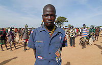 UGANDA Karamoja , Kotido, cattle market, young Karimojong in uniform shirt