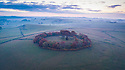 19/10/18<br /> <br /> ***With Video***<br /> <br /> Stunning drone photograph of dawn breaking over Minninglow in the White Peak area of the Derbyshire Peak District.<br /> <br /> Minninglow is the largest and most prominently sited cairn in the Peak District, just over a mile to the west of Aldwark. Surrounded by a beech plantation between the villages of Parwich and Elton, it is a landmark for miles around. <br /> <br /> Measuring 111ft  by 144ft, the cairn consists of at least four chambers and has undergone a number of construction phases. The Low originally began life as a single chamber with a small mound comprised mainly of limestone probably during the Neolithic period. It was later covered by a long cairn with four chambers and later still converted into a massive circular mound, perhaps during the Bronze Age. <br />  <br /> Rod Kirkpatrick holds a PfCO and had permission from the landowner to fly over the site.<br /> <br /> All Rights Reserved, F Stop Press Ltd. (0)1335 344240 +44 (0)7765 242650  www.fstoppress.com rod@fstoppress.com