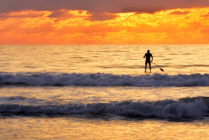 Silhouette of a Surfer Paddling into a Fiery Sky - At Sunrise at Cocoa Beach Florida