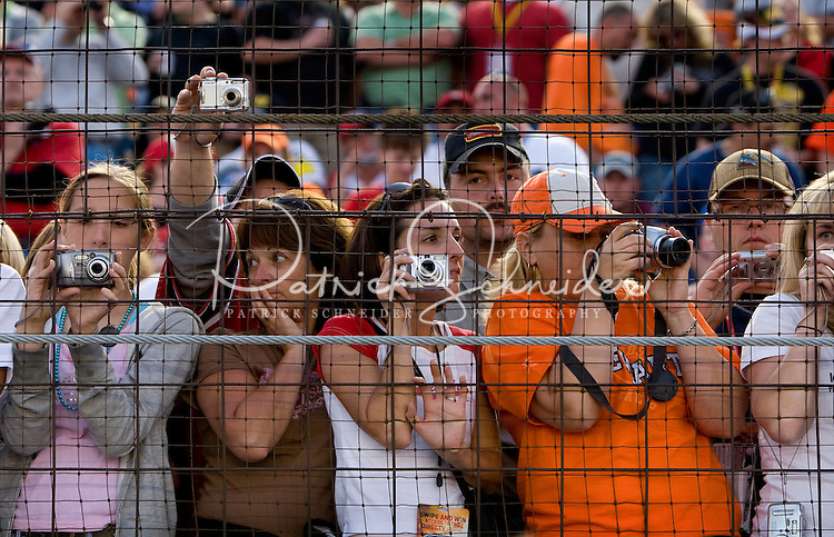 Fans try to get a picture of the drivers during the Bank of America 500 NASCAR race at Lowes's Motor Speedway in Concord, NC.