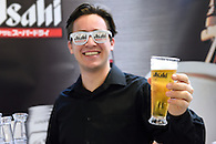 A bartender holding a cold glass of beer at a marketing event for Asahi Beer.