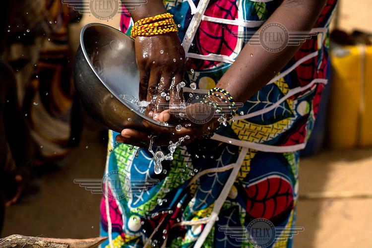 A woman washing a bowl at a nomadic Fulani encampment in Garinbale.