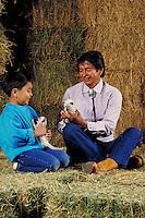 NATIVE-AMERICAN GRANDFATHER AND GRANDSON PLAYING WITH KITTENS IN A BARN. GRANDFATHER AND GRANDSON. OAKLAND CALIFORNIA USA PARK.
