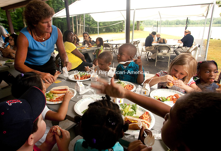 WATERBURY, CT 14  JULY, 2010-07140JS01-Kelly Cronin, Executive Director for Waterbury Youth Services, left, helps kids at the 3-5 year old kids table during a luncheon Wednesday at the Kiwanis Youth Camp in Wolcott. The lunch was held with dignitaries for kids sponsored by Waterbury Youth Services, the Kiwanis Club, the Waterbury Police Activities League and the Campership Fund. The programs help to send inner city kids camp. Waterbury Youth Services and PAL have teamed up to help send these kids to the Kiwanis Youth Camp for an 8-week camp program.<br /> Jim Shannon Republican-American