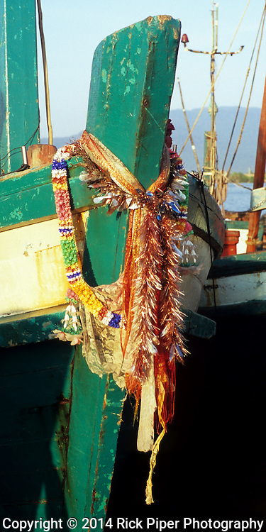 Prow of colourful traditional Cham fishing boat adorned with garlands and scarves, Sanke river at dawn, Kampot, Cambodia.
