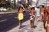 Rio de Janeiro, Brazil. Women in bikinis walking on the Copacabana pavement shading their eyes from the sun with newspapers.