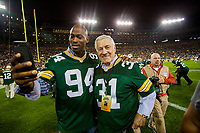 Former Packers Kabeer Gbaja-Biamila and Jim Taylor take a selfie at Lambeau Field after alumni introductions prior to the kickoff betwen the Seattle Seahawks and the Packers on Sept. 20, 2015.
