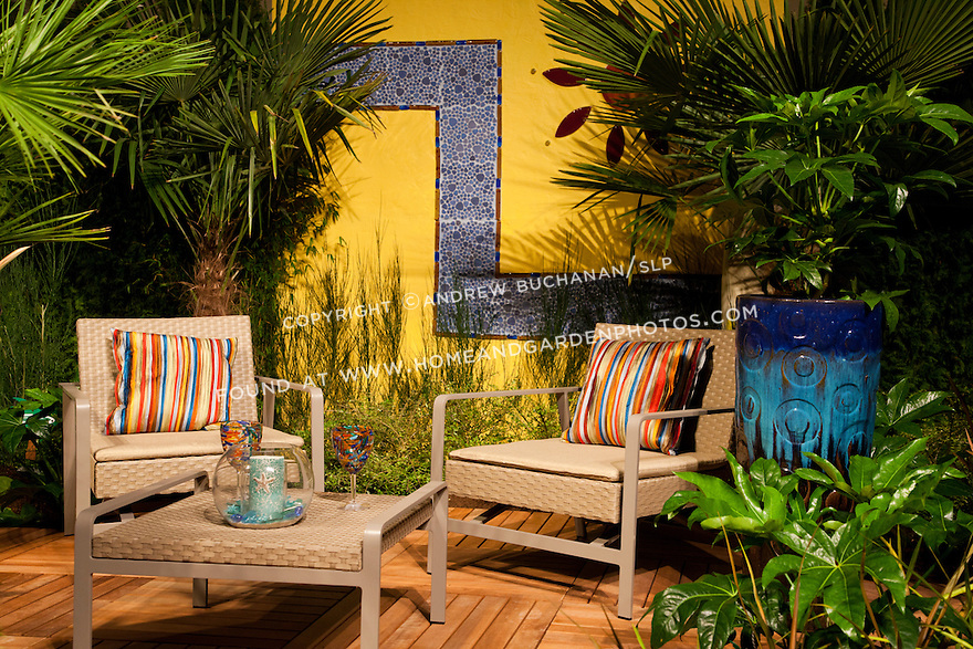 A bright yellow wall with a blue tile inset provides a pop of color in this garden seating area.