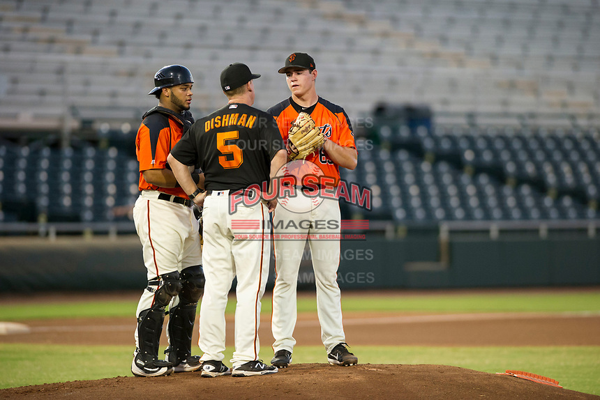 AZL Giants starting pitcher Seth Corry (63) is visited by catcher Jeffry Parra (5) and pitching coach Glenn Dishman (5) during a game against the AZL Rangers on August 22 at Scottsdale Stadium in Scottsdale, Arizona. AZL Rangers defeated the AZL Giants 7-5. (Zachary Lucy/Four Seam Images via AP Images)