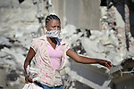 Her nose covered because of the smell of decomposing bodies trapped in the rubble, a woman walks in Port-au-Prince, Haiti, much of which was devastated in a January 12 earthquake.