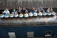 Fishermen, on their journey to market in Dhaka, line the train roof with their pots full of fish. They hope to avoid the 60 taka (£0.55GBP) fare by using the roof and since they can only earn a maximum of 120 taka (£1.10GBP) from their fish the saving is vital. In Bangladesh many people ride on the roofs of trains as frequently that is the only space available. For others, the fares are too high and can be avoided or reduced by travelling on the roof. However, this practice also leads to regular accidents, many of them fatal..