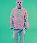 Old man in PJ's on green background