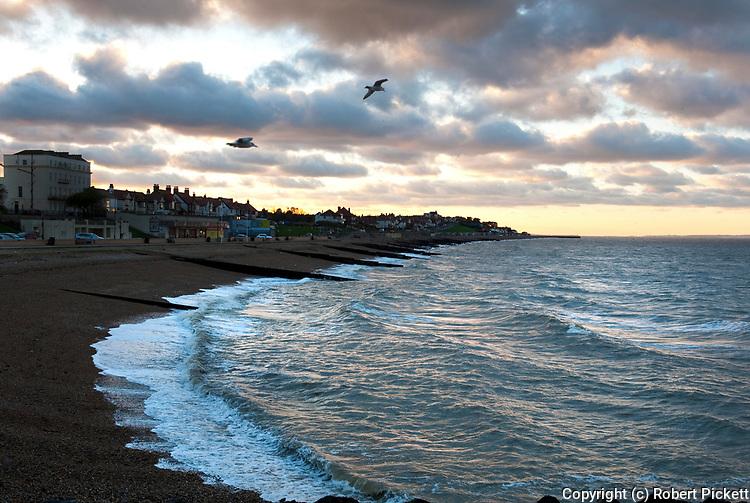 Landscape of Coastline, Herne Bay, Kent UK, showing shingle beach and waves at high tide, sunset