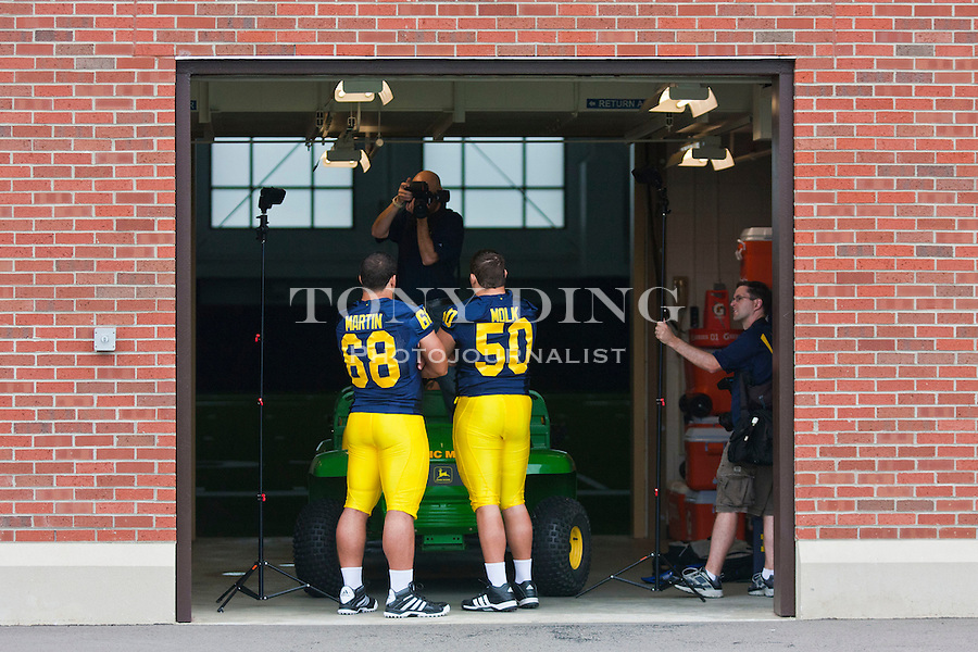 Michigan defensive tackle Mike Martin (68) and offensive lineman David Molk (50) have their photos taken at the annual NCAA college football media day, Sunday, Aug. 22, 2010, in Ann Arbor, Mich. (AP Photo/Tony Ding)