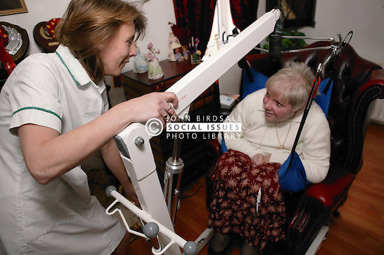 Carer using a hoist to help a patient out of her chair at home; homecare for the disabled,