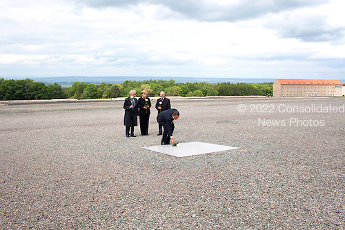 Buchenwald, Germany - June 5, 2009 -- United States President Barack Obama, with Holocaust survivor Elie Weisel,  Chancellor Angela Merkel of Germany and Bertrand Herz, places a rose on a memorial plaque during a visit to the former Buchenwald Nazi concentration camp June 5, 2009..Mandatory Credit: Pete Souza - White House via CNP