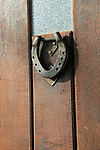Close up of metal horse shoe door knocker in wooden front door, UK