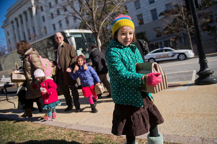 UNITED STATES - JANUARY 28: Naomi Sherman, 4, right, along with her father Rep. Brad Sherman, D-Calif., mother Lisa, and sisters Lucy, 2, and Molly, 5, prepares to board a bus in the Rayburn horseshoe that will take House democrats and their families to a retreat in Philadelphia, January 28, 2015. (Photo By Tom Williams/CQ Roll Call)