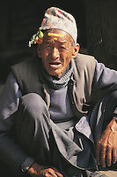 An old man in Bhaktapur, Nepal, his forehead marked with holy paste from his visit to a Hindu temple earlier in the day and his lined and wrinkled face offset by a sprig of flowers behind his ear.