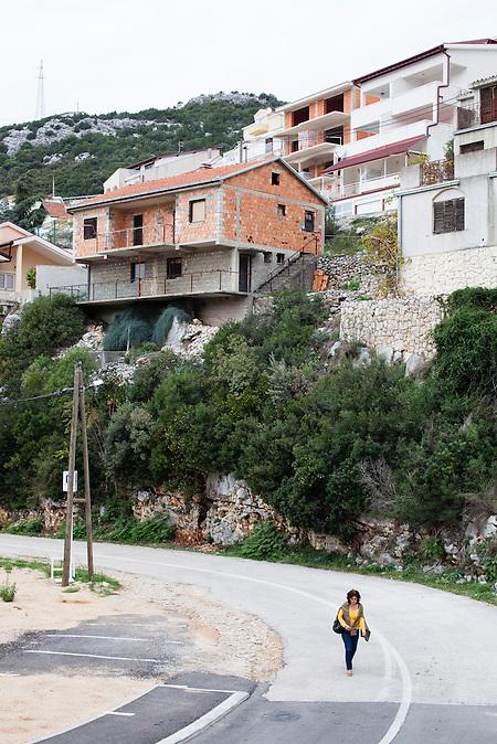 Eine Frau passiert eine leere Straße in Neum. Obwohl die Stadt droht, vom touristischen Straßennetz abgekoppelt zu werden, werden trotzdem weiterhin Häuser gebaut. Der kleine Ort Neum liegt in Bosnien-Herzegovina und bildet den einzigen Zugang zum Meer des Balkanlandes. Auf einer Länge von 9 km durchschneidet der Ort das kroatische Staatsgebiet (Neum-Korridor) Seit dem EU-Beitritt Kroatiens ist Neum auf beiden Seiten von EU-Außengrenzen eingeschlossen. / A woman passes an empty street in Beum, Bosnia. Although the citiy is in danger to be cut off od the adraitc-highway, people still continue to build new houses. The small city of Neum in Bosnia and Herzegovina is the only place in Bosnia, where the country has access to the adriatic sea. Over a length of 9 kilometers the area cuts Croatian territory in two pieces. Since Croatia became part of the European Union, the city of Neum is enclosed between two EU-boarders.