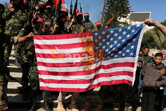 Palestinian militants of the National Resistance brigades, the armed wing of the Democratic Front for the Liberation of Palestine (DFLP), burn US flag during a military parade against US President Donald Trump's decision to recognise Jerusalem as the capital of Israel, in Gaza city on December 9, 2017. Photo by Ashraf Amra