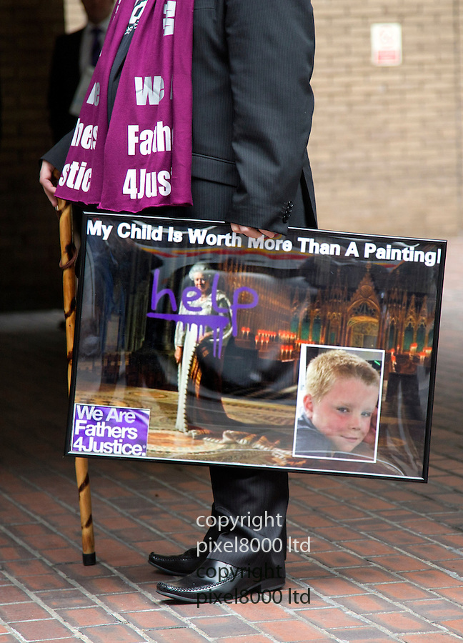 """Tim Haries  appearing at Southwark Crown Court today. 17.9.13<br /> <br /> Pic shows:  Behind him is a mock up of the defaced painting with the words """"help"""" across a portrait of the queen that Haries was allegedly planning to complete<br /> <br /> A Fathers4Justice campaigner appeared in court today accused of defacing a portrait of the Queen in Westminster Abbey.<br /> <br /> Tim Haries, 41, is alleged to have smuggled a can of spray paint into the abbey yesterday before defacing the picture.<br /> <br /> He appeared at Court charged with criminal damage of more than £5,000.<br /> <br /> <br /> <br /> <br /> Pic by Gavin Rodgers/Pixel 8000 Ltd"""