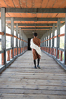 Bhutan, Paro. Man walking on covered bridge.