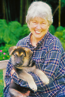 Portrait of a senior woman with puppy in a garden setting