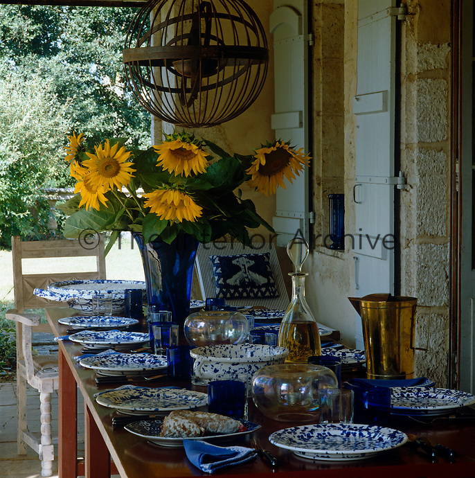 A table laid for a simple lunch on the shady terrace is covered in blue and white splatterware plates from Austria