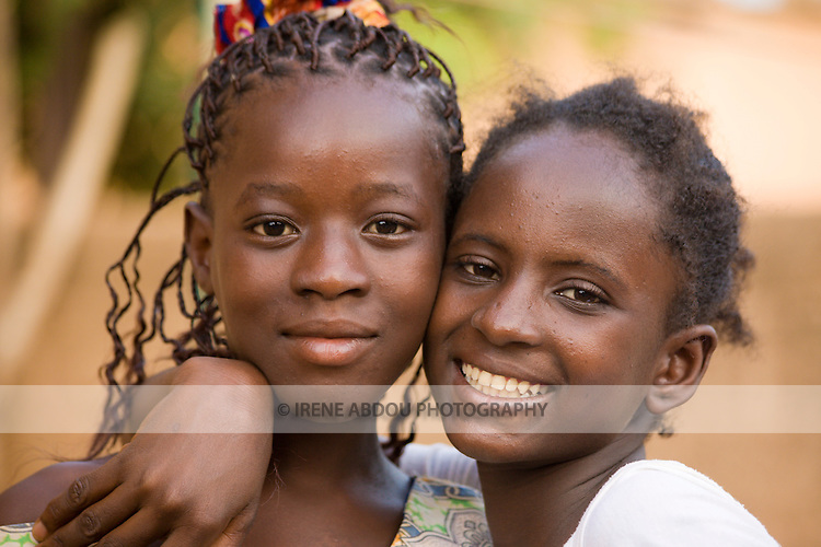 A woman from the Fulani ethnic group (right) hugs her Mossi neighbor (left) in Ouagadougou, the capital of Burkina Faso.