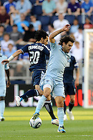 Davide Chiumiento (navy) Vancouver Whitecaps and Graham Zusi Sporting KC challenge for the ball in midfield... Sporting KC defeated Vancouver Whitecaps 2-1 at LIVESTRONG Sporting Park, Kansas City, Kanas.