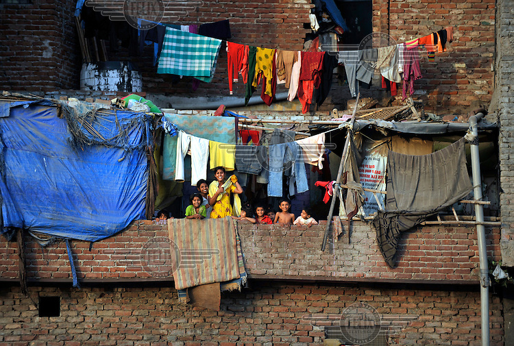 A family outside their home underneath their washing lines in a slum in the area of Nizamuddin East.