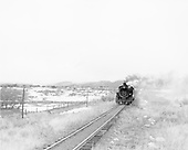 Train approaching.  Open fields and snow.<br /> D&amp;RGW    Taken by Richardson, Robert W. - 1954-1955