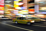 Panned image of Japanese taxi with bright, colorful lights in the background.