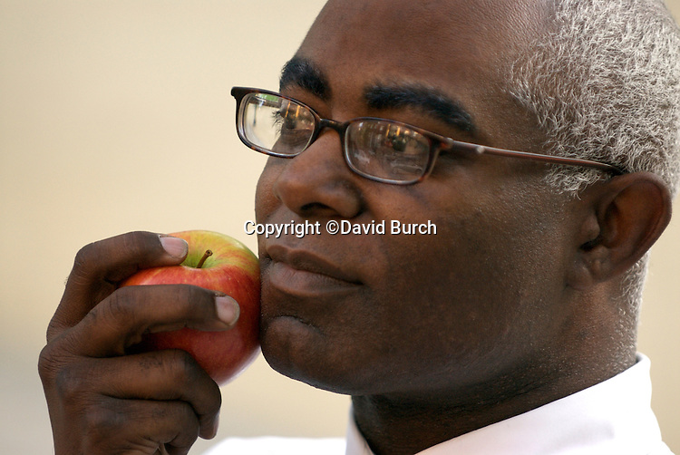 African American man with apple pressed to his cheek, thoughtful,