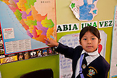 Arequipa, Peru. A. Antoniano (public elementary and secondary school). Portrait of student (girl, elementary-school aged, Peruvian) pointing to her country (Peru) on a poster map of South America. No MR. ID: AL-peru.