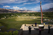 Tourists take photos at a monastery outside of Leh in Ladakh region in Kashmir, India.