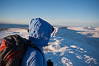 Hiker looking across winter landscape from summit of Pen Y Fan, Brecon Beacons national park, Wales