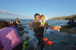 A refugee father carries his child ashore on a beach near Molyvos, on the Greek island of Lesbos, on October 30, 2015, after they crossed the Aegean Sea from Turkey in a small overcrowded boat provided by Turkish traffickers to whom the refugees paid huge sums. The refugees were received in Greece by local and international volunteers, then proceeded on their way toward western Europe.