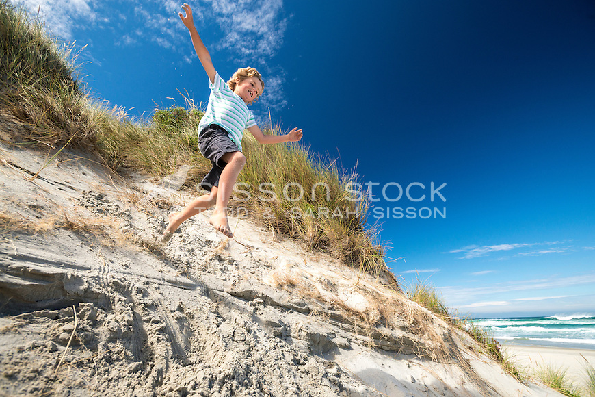 Young boy leaping in the sand dunes at Tomahawk Beach on a blue sky day, Dunedin, Otago, South Island, New Zealand - stock photo, canvas, fine art print