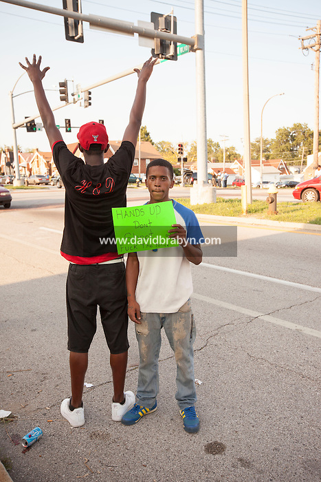 HSUL 20140819 United States, St Louis, MO. Eric Evans holds up a sign that reads 'Hands up, Don't Shoot. Fuck the police', as he stands nearby to where St. Louis police say officers shot and killed a 23-year-old man who was wielding a knife and refused to drop it on August 19, 2014 in St Louis, Missouri. Photographer: David Brabyn