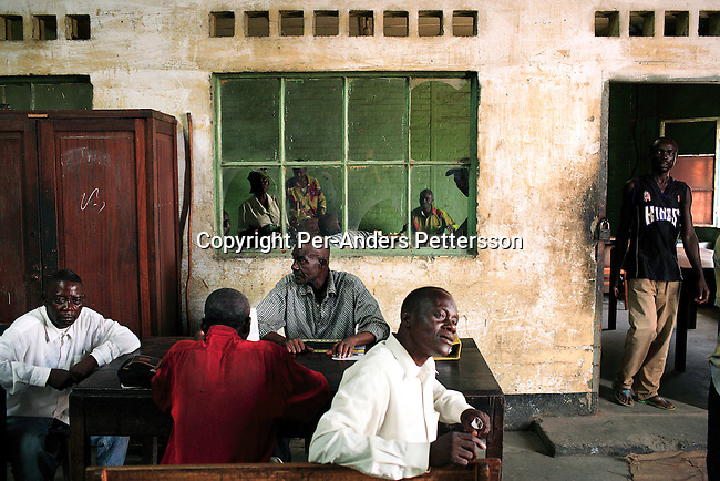 KINSHASA, DEMOCRATIC REPUBLIC OF CONGO MAY 4: Unidentified men drink tea and bread in an office in an idle harbor on May 5, 2006 in Kinshasa, Congo, DRC. The port is run by the state company ONATRA, and is in shambles. Ships and equipment is rusting and has been idle for many years. Many workers show up for work every day but have nothing to do. The port collapsed in early 1990, and the problem was made worse when former president Mobuto Sese Seko gave up power in 1997, and a civil war erupted. Kinshasa, a city of about eight million people is battling with bad infrastructure and no public transport. The country is planning to hold general elections by July 2006, the first democratic elections in forty years..(Photo by Per-Anders Pettersson/Getty Images)....