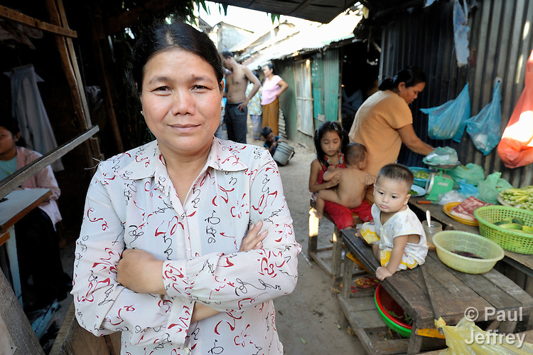 A member of a women's self-help group, Morn Nen, 48, stands in the narrow street in front of her home in the Phnom Penh neighborhood of Sen Rikreay. Many people in this community are infected or affected by HIV and AIDS, and Buddhist monks and other religious meet with them regularly to mediate and discuss their challenges.