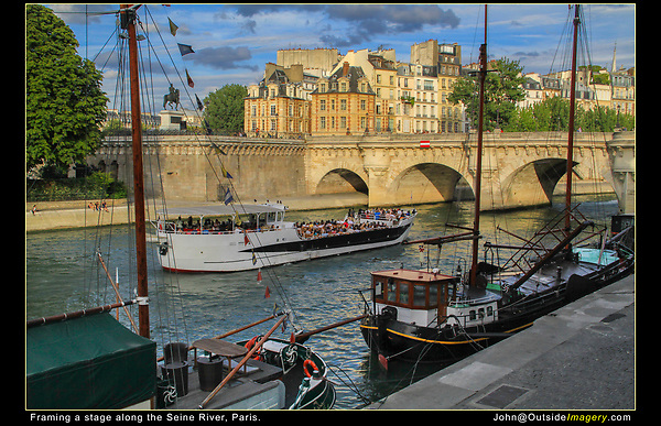 France, Paris. <br /> Make a strong composition with a stage, using vertical lines (the masts) and diagonal lines (foreground boats) for framing. Don't move the camera and let the action move through your scene. Boats on the Seine River.