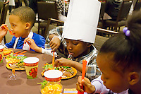 The young chefs enjoy their healthy meal. Children participating in Nourishing NYC's Junior Chef program prepare a healthy Thanksgiving dinner in midtown in New York on Saturday, November 19, 2011.   © (Frances M. Roberts)