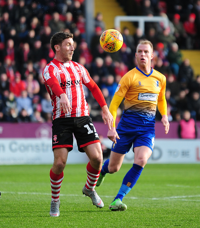 Lincoln City's Shay McCartan shields the ball from Mansfield Town's Neal Bishop<br /> <br /> Photographer Andrew Vaughan/CameraSport<br /> <br /> The EFL Sky Bet League Two - Lincoln City v Mansfield Town - Saturday 24th November 2018 - Sincil Bank - Lincoln<br /> <br /> World Copyright © 2018 CameraSport. All rights reserved. 43 Linden Ave. Countesthorpe. Leicester. England. LE8 5PG - Tel: +44 (0) 116 277 4147 - admin@camerasport.com - www.camerasport.com
