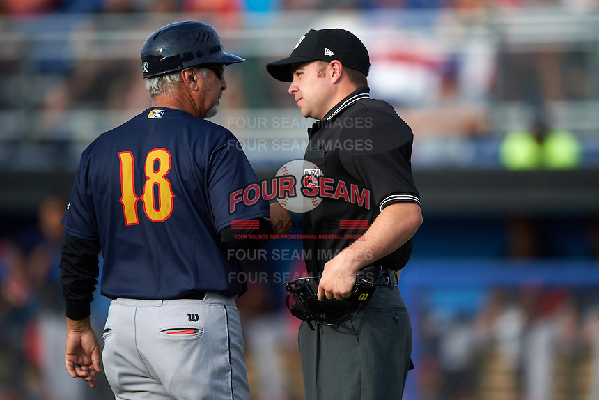 State College Spikes manager Johnny Rodriguez (18) talks with umpire John Budka during a game against the Batavia Muckdogs on June 22, 2016 at Dwyer Stadium in Batavia, New York.  State College defeated Batavia 11-1.  (Mike Janes/Four Seam Images)