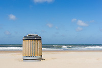 A garbage container on a clean beach