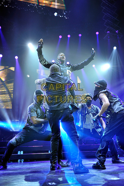 USHER (USHER RAYMOND).Performing live at the O2 Arena, London, England. .February 3rd, 2011.stage concert live gig performance music full length black leather jacket jeans denim backup dancers lifting carrying gesture arms in air .CAP/MAR.© Martin Harris/Capital Pictures.